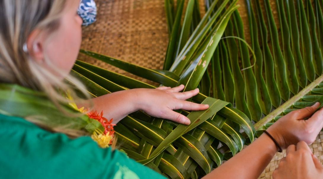 Female Culture and Community Volunteer weaves leaves during her volunteering placement in Fiji.